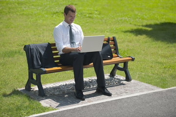 Businessman sitting on bench with laptop