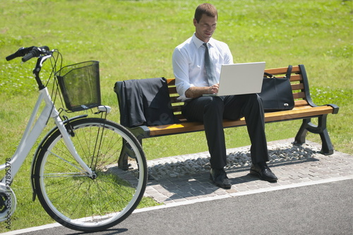 Businessman sitting on bench with laptop and bicycle