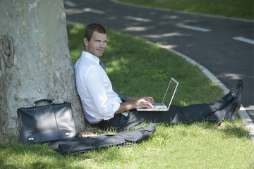 Businessman with laptop working under a tree