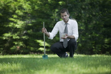 Businessman on lawn with shovel and jar of coins