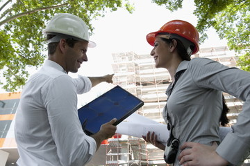 Man and woman with hardhats at construction site