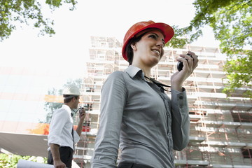 Woman with hardhat and man on walky talky at construction site