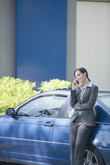 Young woman in suit leaning on car talking on smartphone