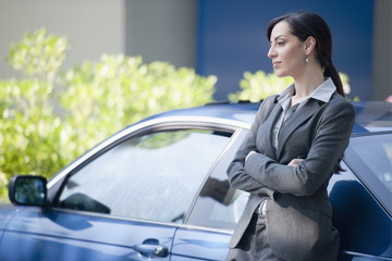 Woman in suit next to car