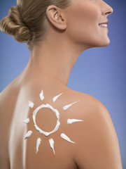 Close-up of young woman with sunscreen in shape of sun on back shoulder,  studio shot
