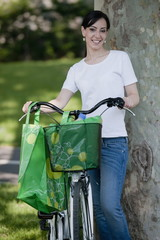 Casual woman with bicycle and reusable shopping bags