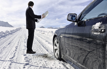Mid adult businessman standing next to car with road map on winter day