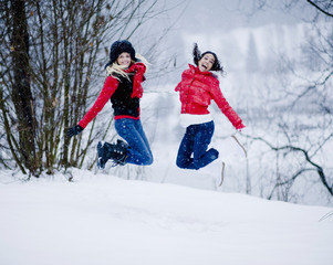 Young women jumping in midair on winter day