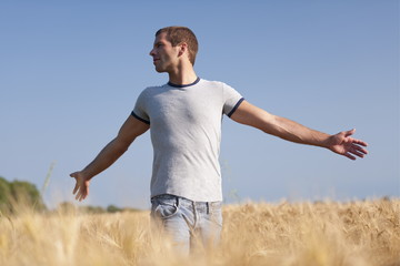 Man with arms stretched out in wheat field