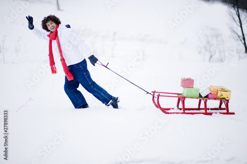 Young man waving and pulling sled in snow