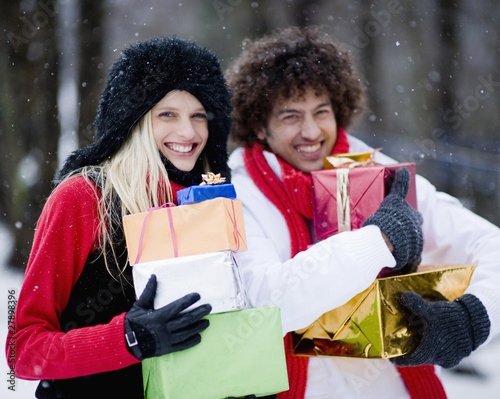 Young couple carrying presents on winter day