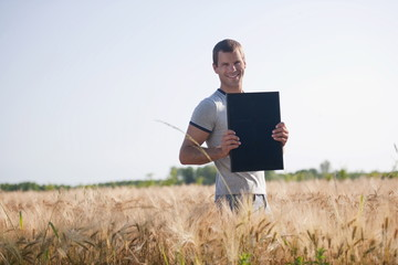 Man holding solar panel in wheat field