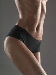 Cropped view of young wet woman in underwear, studio shot