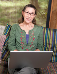 Mature Woman Smiling and Working at Laptop Computer