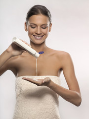 Young woman pouring lotion in hand, studio shot