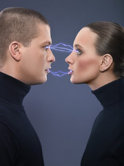 Man and woman staring at each other with electricity going to each other, studio shot