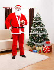Santa Claus standing in front of Christmas Tree
