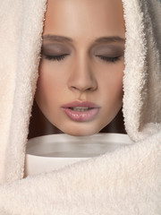 Young woman with towel over head breathing in steam from hot water