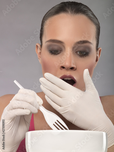 Portrait of shocked young woman eating, studio shot