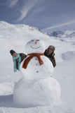 Portrait of young couple with snowman on winter day
