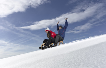 Mid adult couple snow sledding on snow slope