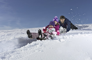 Father pushing daughters on snow sled on winter day