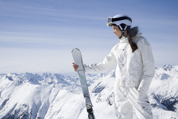 Young woman with skis standing in mountains on winter day