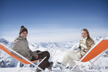 Young couple sitting in lounge chairs in mountains on winter day