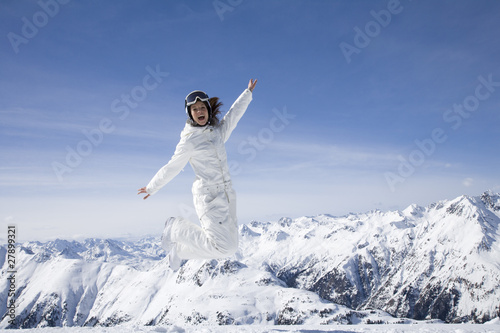 Young woman in ski gear jumping in midair in the mountains