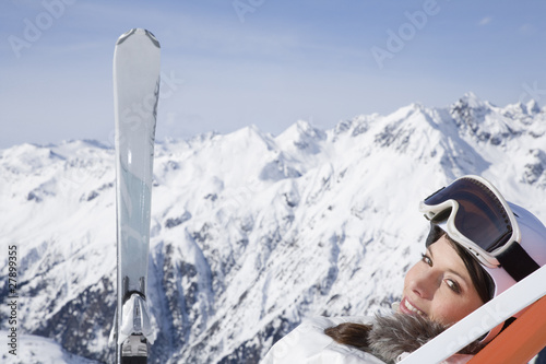 Young woman with skis relaxing in lounge chair in mountains