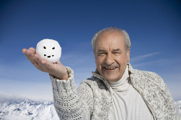 Senior man holding snowball with smiley face on winter day