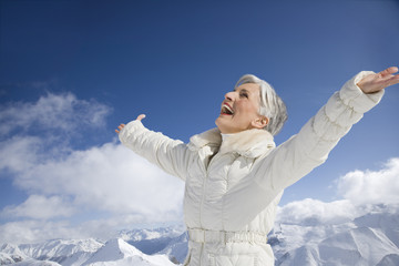 Mature woman with arms wide open on winter day
