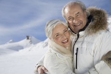 Portrait of happy senior couple in coats on winter day