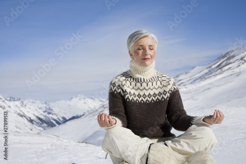Mature woman doing yoga in mountains on winter day