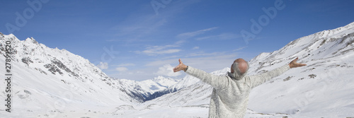 Senior man in winter mountains with arms outstretched