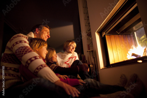 Mid adult family sitting together near fireplace