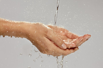 A stream of water splashing onto a woman's hands