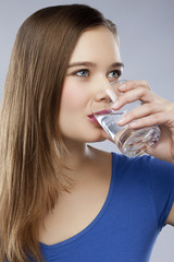 A woman drinking a glass of water