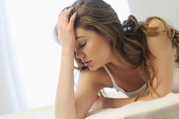A woman lying on a bed looking tired and stressed