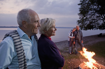 Two senior couples standing beside a campfire