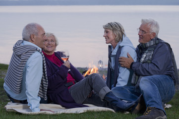 Two senior couples drinking wine and talking beside a campfire