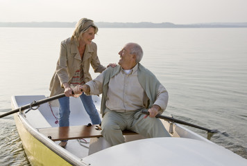 A senior couple rowing on a lake, laughing