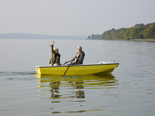 A senior couple in a rowing boat, woman waving