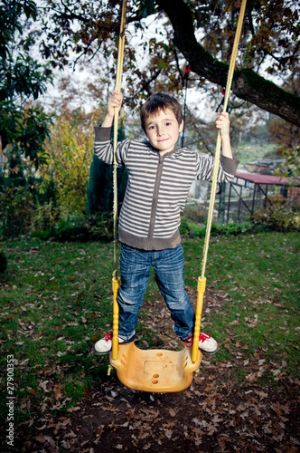 Boy standing on a swing