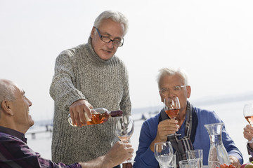 Three senior men drinking wine beside a lake