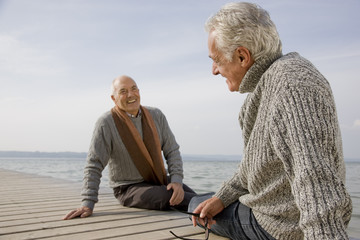 Two senior men sitting on a wooden jetty, Smiling, Toothy Smile
