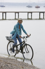 A senior woman riding a bicycle along the shore of a lake
