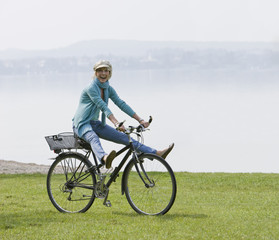 A senior woman, freewheeling on a bicycle