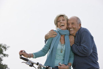 A senior couple pushing a bicycle embracing