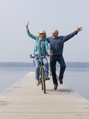 A senior couple on a wooden jetty, woman riding a bicycle